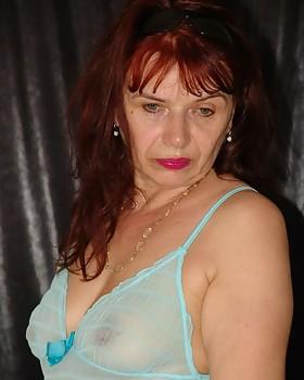Redheaded grandma Christel strips and shows her boobies